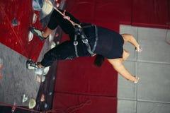 伸出在绳索的活跃愉快的妇女在训练上升的中心 库存照片