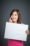 伸出她的舌头的亚洲女孩举行空白标志 图库摄影