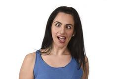 伸出舌头和横渡眼睛的年轻可爱和嬉戏的妇女看起来疯狂 库存照片