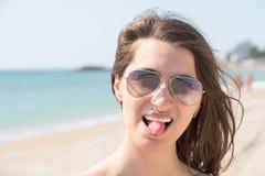 伸出舌头的愉快的少妇在海滩 免版税库存照片