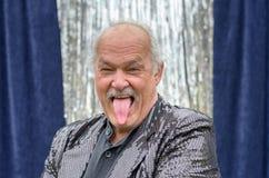 伸出他的舌头的笑的幽默人 免版税库存图片