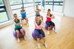 伸在锻炼球的运动的人民手在健身房 免版税库存照片