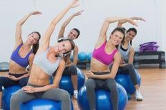 伸在锻炼球的运动的妇女手在健身房 免版税库存照片