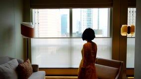 伸她的手的妇女在窗口附近 股票录像