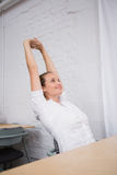 伸手的女实业家在办公室 免版税库存图片