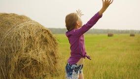 伸手的愉快的女孩对在干草堆背景的天空 举手的少年女孩享受在收获的自然 股票视频