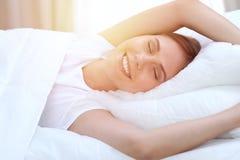 伸手的美丽的年轻和愉快的妇女,当舒适地在床上和有福地微笑前面时醒  免版税库存图片