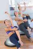 伸手的运动的妇女在瑜伽类 图库摄影