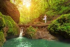 但是,放松,妇女实践瑜伽在瀑布 免版税库存照片