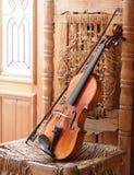位于在一把老和被破坏的椅子的小提琴 库存照片