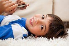 位于在与移动电话的地毯的男孩 库存图片