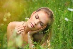 位于在与花的草的女孩 免版税库存照片