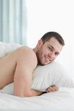 位于在他的腹部的一个微笑的年轻人的纵向 免版税图库摄影