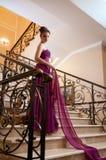 位于在台阶的一件长的礼服的妇女 免版税库存照片