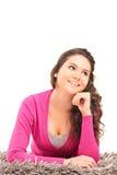 位于在地毯和认为的一个微笑的女性 免版税库存图片