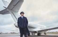 位于在平面室外对面的愉快的飞行员 免版税库存图片