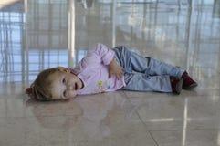 位于在楼层上的疲乏的小女孩 免版税库存照片