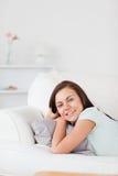 位于在沙发的一名逗人喜爱的妇女的纵向 免版税库存图片