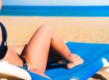 位于在海滩懒人的少妇 免版税库存照片
