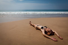 位于在热带海滩的女孩,晒日光浴 图库摄影