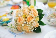 位于在表的橙色玫瑰婚礼花束  免版税库存图片