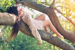 位于在长凳的女孩在森林里 免版税库存照片