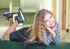 位于在长沙发的女孩 免版税库存图片