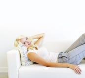 位于在长沙发的妇女 库存照片