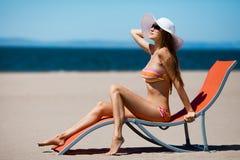 位于在deckchair的美丽的妇女在海滩 免版税图库摄影