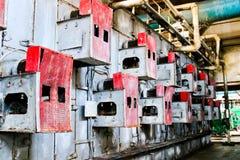 位于墙壁的穿孔的电栅格设备的铁金属红色内阁一个工业石油化学的化工精炼厂 免版税图库摄影