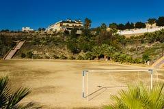 位于山的橄榄球场在村庄附近 库存照片