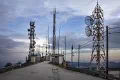位于有天线的小山顶的大量无线电帆柱 无线电帆柱和塔是高结构被设计支持天线 免版税库存照片