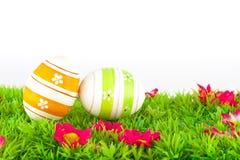 位于有花的一个草甸的五颜六色的被绘的复活节彩蛋 免版税图库摄影