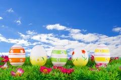 位于有花的一个草甸的五颜六色的被绘的复活节彩蛋 图库摄影