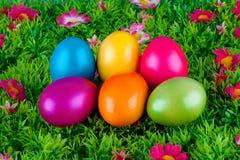 位于有花的一个草甸的五颜六色的被绘的复活节彩蛋 免版税库存图片