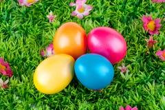 位于有花的一个草甸的五颜六色的被绘的复活节彩蛋 库存图片