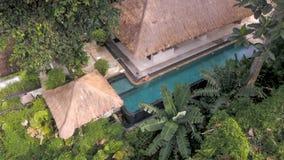 位于有蓝色游泳场和模型的密林的豪华平房别墅Arial射击  免版税库存照片