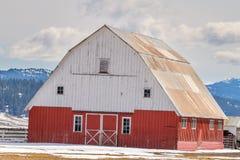 位于有雪的爱达荷农场的独特的红色和白色谷仓 免版税图库摄影