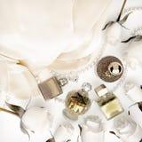 位于白色折叠和珍珠的香水瓶、玫瑰  免版税库存图片