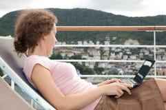 位于的女孩sunbed与在甲板的膝上型计算机 免版税库存图片