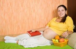 位于的怀孕的沙发妇女 免版税库存图片