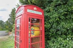 位于老废弃的红色电话亭的去纤颤器 免版税图库摄影