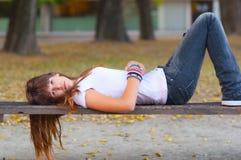 位于长凳的女孩相当哀伤少年 库存照片