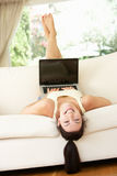位于颠倒在沙发的妇女使用膝上型计算机 图库摄影