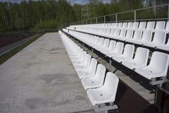 位子蓝色,红色,白色行在体育场的 库存图片