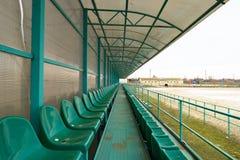 位子行在一个空的体育场内 绿色供以座位体育场 库存图片