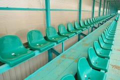位子行在一个空的体育场内 绿色供以座位体育场 库存照片