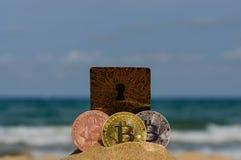 位币金、银和古铜铸造并且打印了被加密的金钱,土窖在海滩沙子的货币概念 库存图片