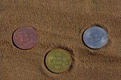 位币金、银和古铜铸造并且打印了被加密的金钱,土窖在海滩沙子的货币概念 库存照片