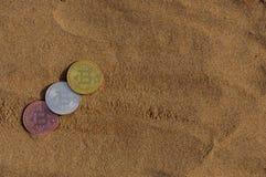 位币金、银和古铜铸造并且打印了被加密的金钱,土窖在海滩沙子的货币概念 免版税库存照片